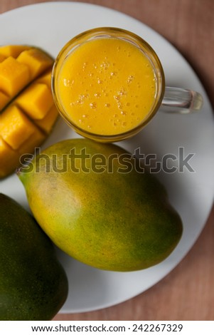 Top view of fresh mango smoothie with ripe mangoes on the white plate - stock photo