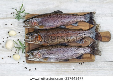 Top view of fresh trout being prepared, skin coated with oil, for cooking on server board. Herbs and spices on white aged wooden boards.  - stock photo