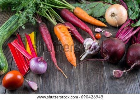 Top view of fresh vegetables, spices on rustic dark background. Carrot, beet, chard, zucchini, onion, garlic, tomato. Harvest/gardening concept.