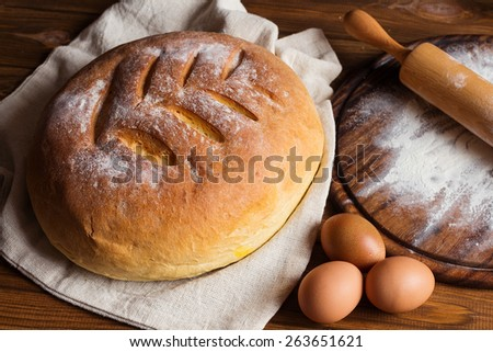 Top view of freshly baked homemade bread with eggs, flour and rolling pin  on rustic wooden table. Low key still life with natural lighting. Shallow focus - stock photo