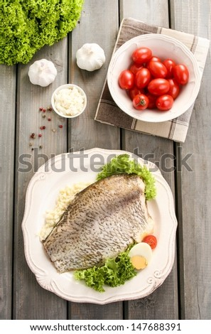 Top view of fried cod on white plate with fresh vegetables and egg, on old wooden table. Tomatoes and other fresh vegetables in the background. - stock photo