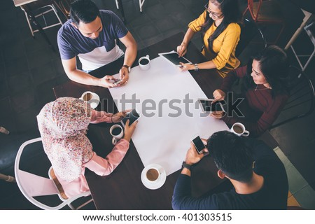 top view of friends at a cafe with all people busy with their own digital devices. blank white paper at the middle - stock photo