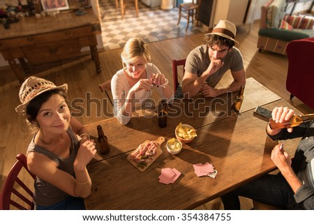 Top view of friends having a drink and playing cards on a sunny evening. They are sitting at a wooden table in a cozy house with beers and tortilla chips. They are wearing casual clothes and hats. - stock photo