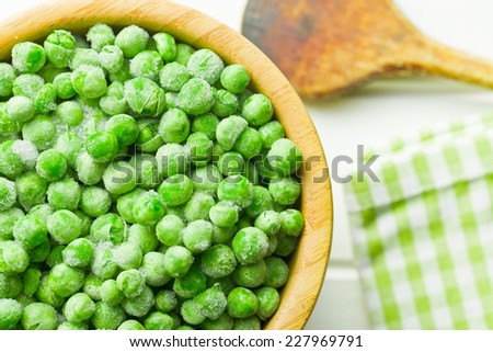 top view of frozen peas in wooden bowl - stock photo