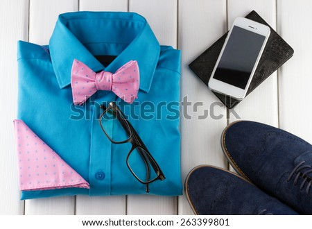 Top view of gentlemanly set: shoes, shirt, bow tie, scarf, glasses, smartphone, passport on white wooden background - stock photo