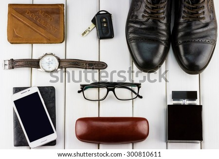 Top view of gentlemanly set: watches, auto document, car keys, shoes, glasses, smartphone, perfume on white wooden background - stock photo