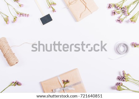 Top view of gifts in package, decorations and flowers on white table