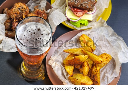 Top view of glass of beer, fries, sandwich and chicken legs on black slate stone - stock photo
