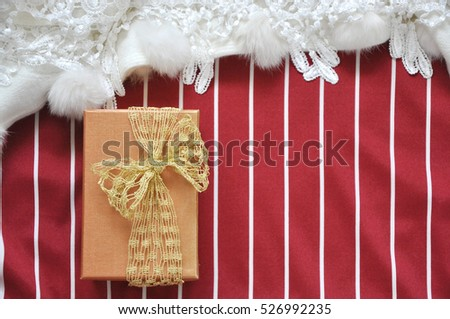 Top view of golden gift box on red and white stripe background with copyspace