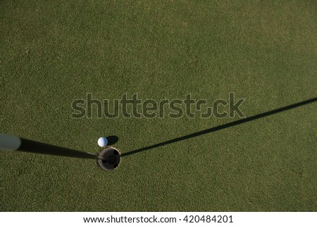 top view of golf ball on edge of course hole representing achivement and success business concept - stock photo