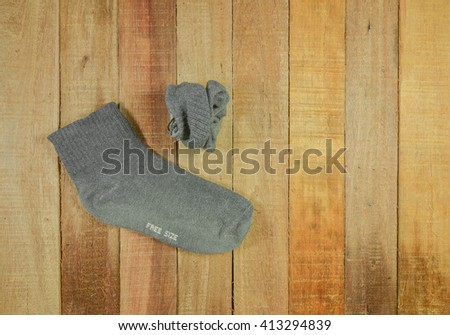 Top view of gray socks on wood background.
