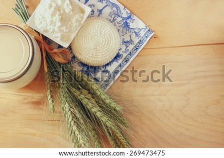 top view of greek cheese , bulgarian cheese and milk on wooden table over wooden textured background. Symbols of jewish holiday - Shavuot  - stock photo