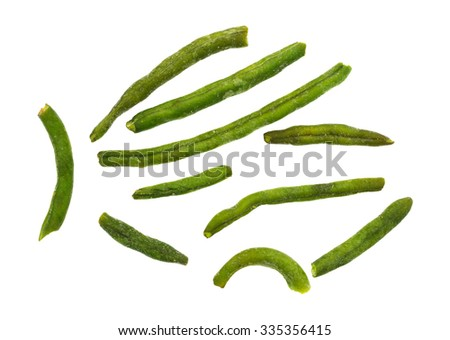Top view of green beans that have been dehydrated and salted arranged on a white background.