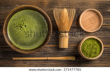Top view of green tea matcha in a bowl on wooden surface - stock photo