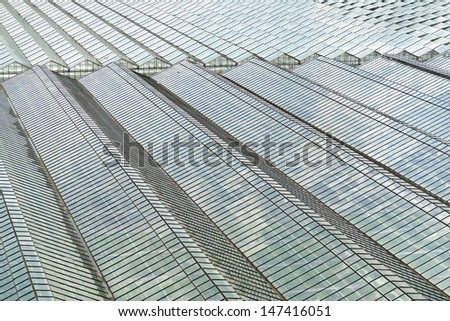 Top view of greenhouses, with lots of glass, and nice reflection of the sky. - stock photo