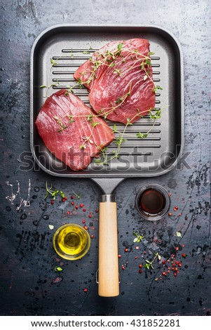 Top view of  grill frying pan with two raw tuna steaks, oil and fresh seasoning on dark aged vintage background. Seafood concept - stock photo
