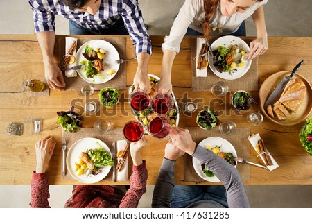 Top view of group of friends raising a toast post lunch. High angle view of happy men and women celebrating at home with red wine. Close up shot of friends toasting glasses of red wine in a party. - stock photo
