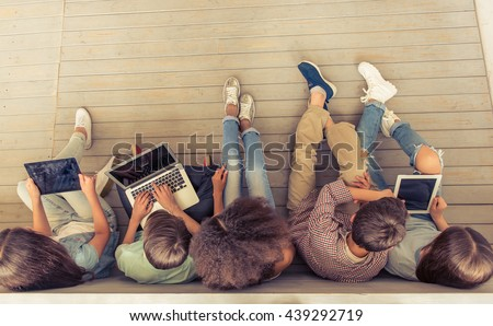 Top view of group of teenage boys and girls using gadgets while sitting in row on wooden floor - stock photo