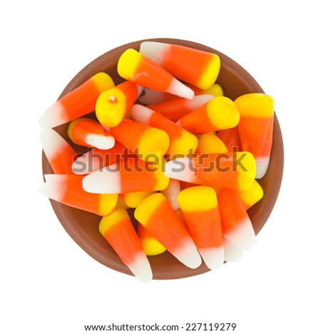 Top view of Halloween candy corn kernels in a small bowl on a white background. - stock photo