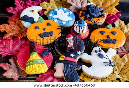 Top view of halloween cookies with colorful decorations on fake autumnal leaves.