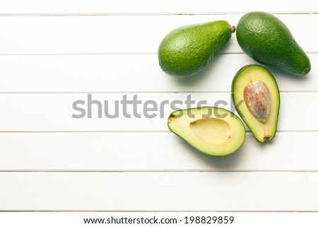 top view of halved avocados on wooden background - stock photo