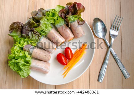 Top view of Ham roll  salad with lettuce, tomato, egg put near Spoon and fork.clean food and fresh vegetable. - stock photo