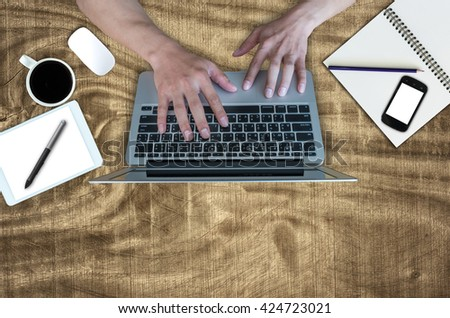 Top view of hand using the laptop with Office Supplies on wooden table background, flat lay, Business concept