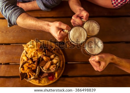 Top view of hands clanging glasses of beer together, near big wooden tray with delicious snacks, on wooden background - stock photo