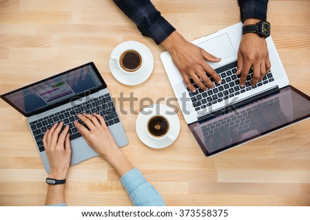 Top view of hands of african man and caucasian woman typing on two laptops and drinking coffee on wooden table - stock photo