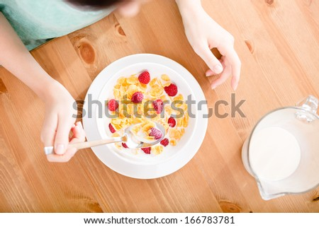 Top view of hands of the girl eating cereals with strawberry and milk