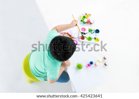 Top view of handsome boy holding brush drawing. shooting in the studio on white background. - stock photo