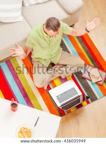Top view of handsome man sitting on floor and using laptop computer. Happy businessman thinking about new business projects.