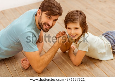 Top view of handsome young father in casual clothes and his cute little son competing in arm wrestling while lying on a wooden floor in the room - stock photo