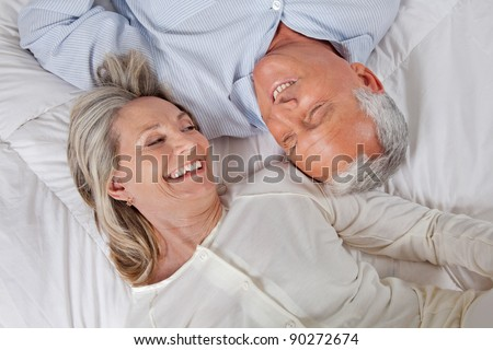 Top view of happy couple lying in bed - stock photo