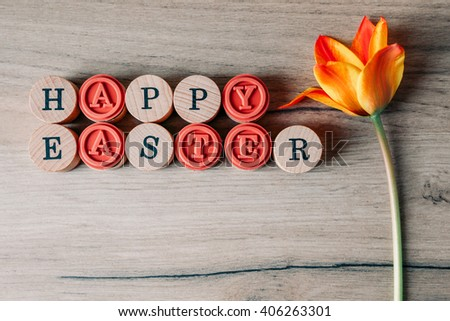 Top view of Happy Easter text with tulip flower decoration - stock photo