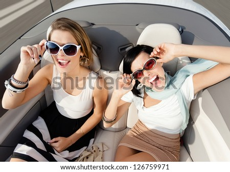 Top view of happy women with sunglasses sitting in the cabriolet - stock photo