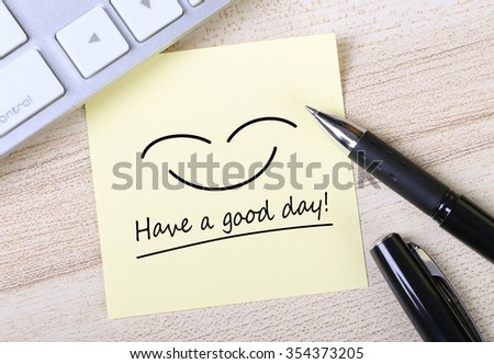 Top view of Have a good day sticky note pasted on the wooden desk with keyboard and pen aside. - stock photo