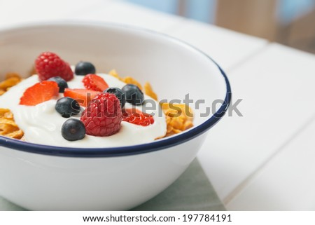 Top view of healthy breakfast with cereals, berries, honey and nuts in an enamel bowl on a white wood background