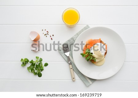Top view of healthy breakfast with poached eggs royale (benedict), fresh orange juice and green salad - stock photo