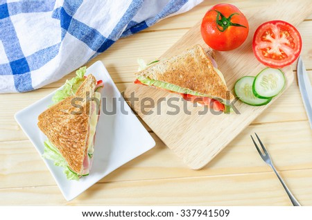 Top view of Healthy Sandwich in white dish with cucumber and tomato on wooden board - stock photo