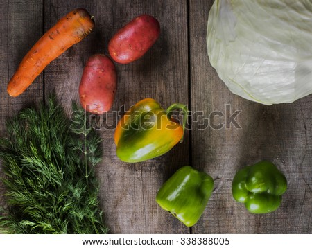 Top view of Heap of Raw Vegetables with Cabbage, Potatoes, Carrot, Green Bell Peppers,  and Dill on old weathering wooden table - stock photo