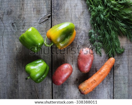Top view of Heap of Raw Vegetables with Potatoes, Carrot, Green Bell Peppers,  and Dill on old weathering wooden table - stock photo