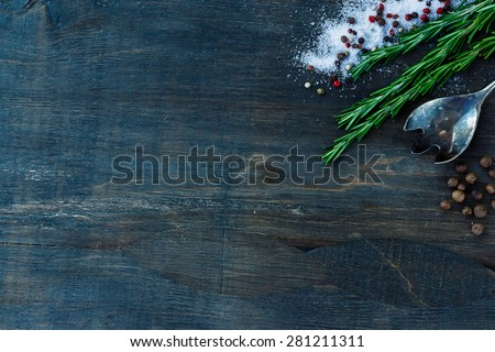 Top view of herbs and spices (rosemary, salt and pepper) on dark wooden background. - stock photo