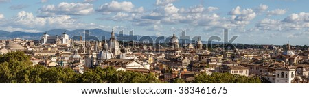 Top view of historical city of Rome with domes, on cloudy blue sky background.