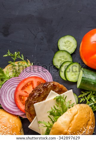 top view of homemade burger ingredients on black board with copy space - stock photo