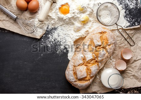 top view of homemade gluten free bread with ingredients on black board with copy space - stock photo
