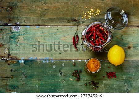 Top view of Hot Chili Peppers in glass jar with herbs and spices over rustic wooden board - cooking or spicy food concept. Background with space for text. - stock photo