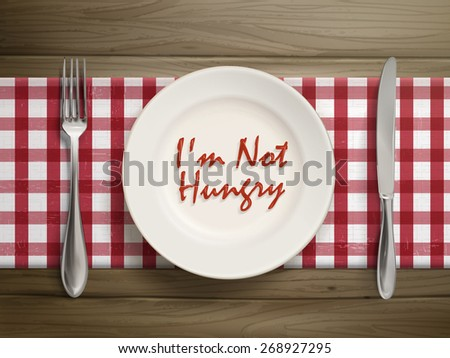 top view of I am not hungry written by ketchup on a plate over wooden table - stock photo