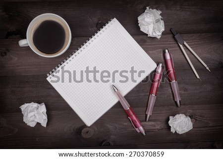 Top view of idea concept with pencils, notepad, coffee cup and crumpled paper on a black wooden table - stock photo