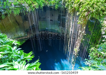 Top view of Ik-Kil Cenote, near Chichen Itza, Mexico. Lovely cenote with transparent waters and hanging roots - stock photo